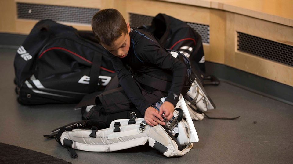 young goalie putting on equipment
